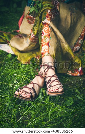 woman legs  on grass in strap flat sandals and boho style silky  dress  closeup