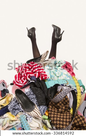 Woman legs reaching out from a big pile of clothes and accessories. Woman buried under an untidy cluttered woman wardrobe. Woman in high heels needs help from to much shopping. Shopaholic girl. - stock photo