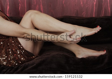 Woman legs sitting down wearing party dress - stock photo