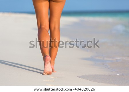 Woman legs walking on the beach sand  - stock photo