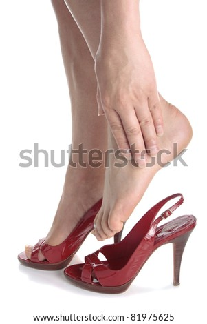 Woman legs wearing high heels massaging aching feet over white background
