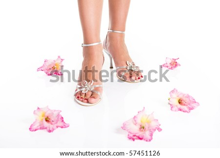 Woman legs with red manicure on the feet and flowers
