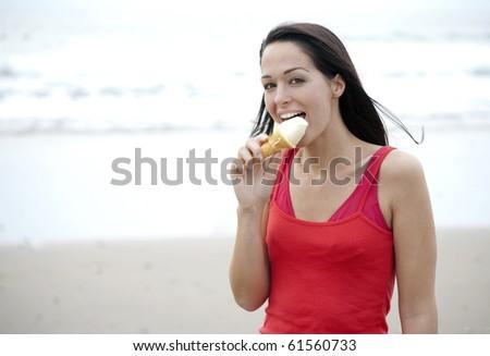 Woman licking ice cream at the beach - stock photo