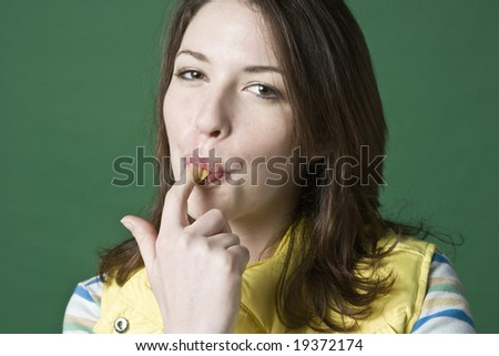 Woman licking peanut butter from her finger - stock photo