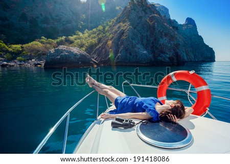 Woman lies on a boat in the blue dress. Active leisure on a yacht at sea. - stock photo