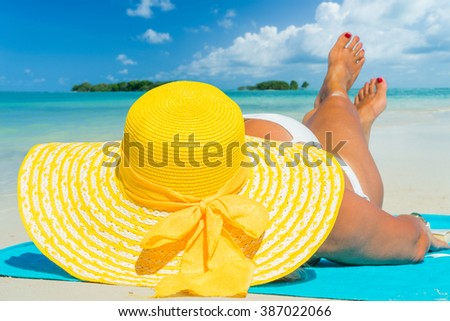 Woman lies on the beach with yellow hat and blue towel - stock photo
