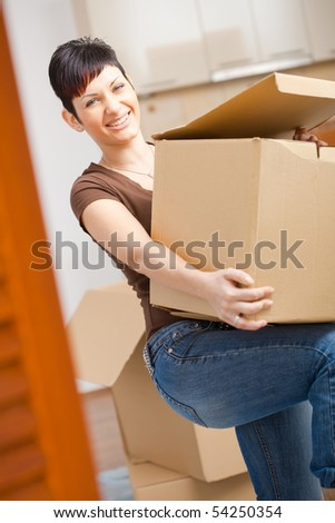 Woman lifting cardboard box while moving home, smiling. - stock photo