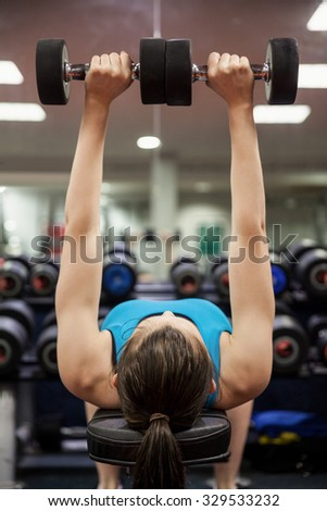 Woman lifting dumbbell weights while lying down at the gym - stock photo