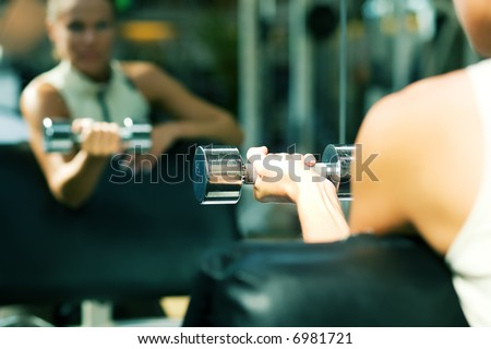 Woman lifting dumbbells in a gym, seeing herself in a mirror (focus only on the dumbbell) - stock photo