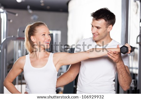 Woman lifting dumbbells while instructor assisting her - stock photo