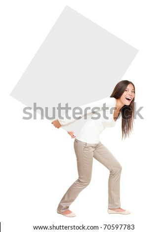 Woman lifting / showing heavy blank billboard sign. Woman carrying empty sign board on her back. Funny image of beautiful asian \ caucasian female model isolated in full length on white background. - stock photo