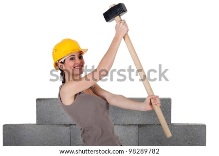 Woman lifting sledge-hammer in front of unfinished wall - stock photo