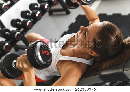 Woman lifting weights and working on her chest at the gym - stock photo