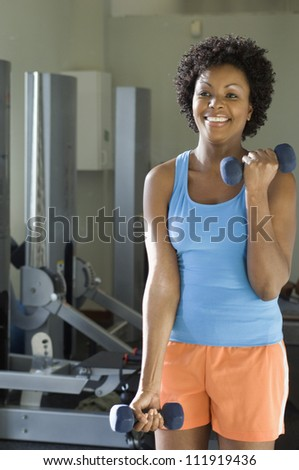 Woman lifting weights at a gym - stock photo