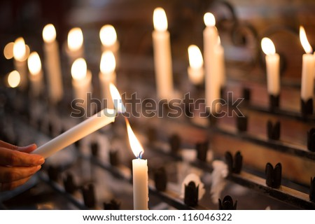 Woman lighting prayer candle aka offering, sacrificial or memorial candles lit in a church - stock photo