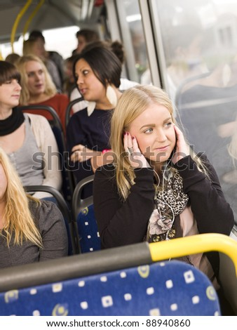 Woman listen to music while going by the bus - stock photo