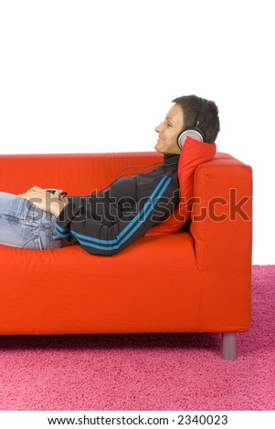 woman listen to the music on the red sofa - stock photo