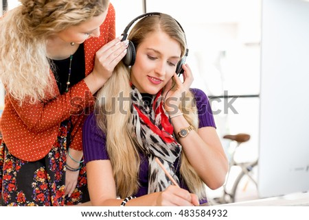 Woman listening in headphones with her colleague