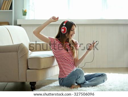 Woman listening music in headphones in room - stock photo