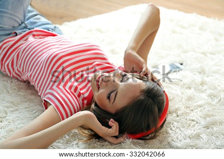 Woman listening music in headphones while lying on carpet in room - stock photo