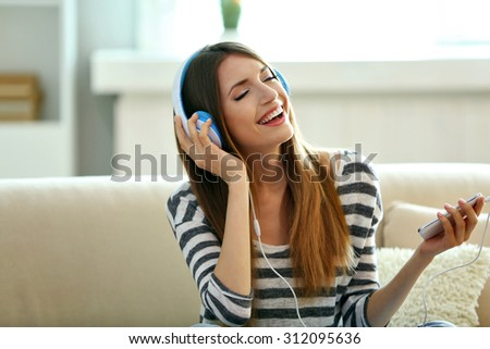 Woman listening music in headphones while sitting on sofa in room - stock photo