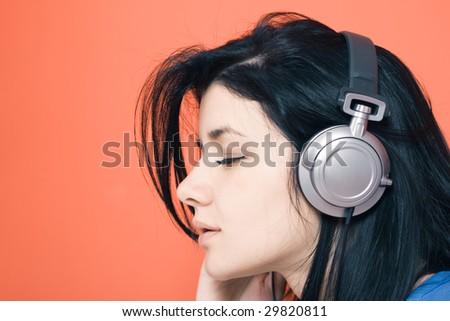 Woman listening music on headphones - stock photo