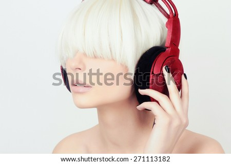 Woman listening music on headphones. Closeup portrait of beautiful girl with bob hair.Red headphones - stock photo