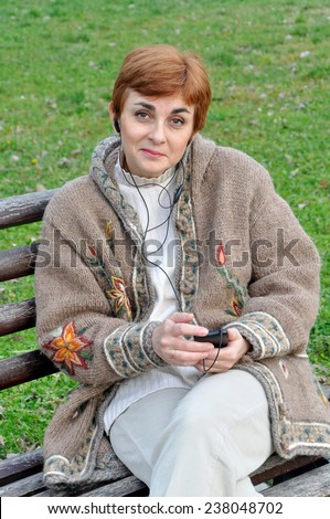 Woman listening to music and sitting on the bench in the city park   - stock photo