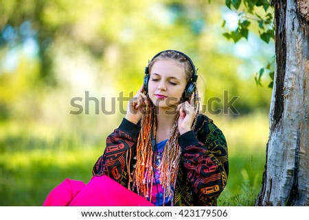 Woman listening to music. Female student girl outside in park listening to music on headphones while studying. Happy young university student of mixed Asian and Caucasian ethnicity. - stock photo