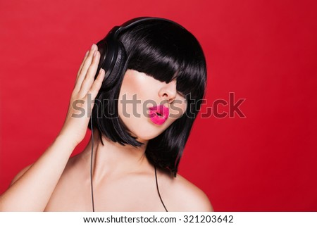 Woman listening to music on headphones enjoying a dance on red background - stock photo