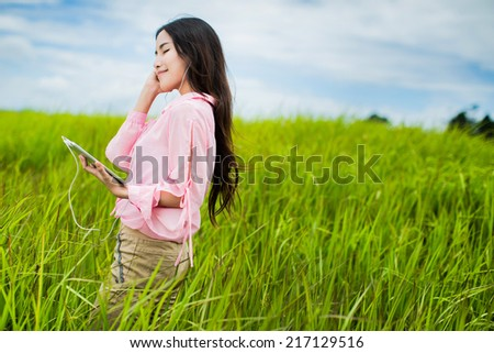 Woman listening to music on meadow - stock photo