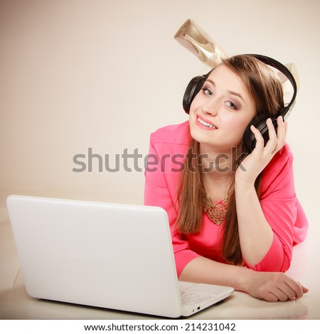 Woman listening to music with headphones and using computer laptop. Student girl learning language with new technology. - stock photo