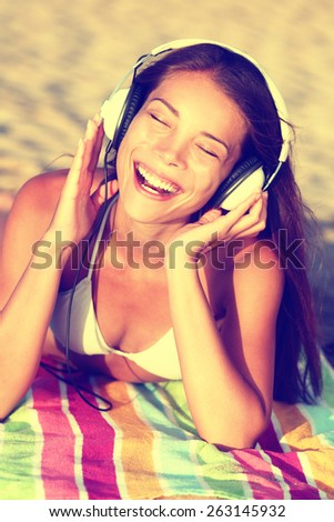 Woman listening to music with headphones at beach. Young Asian girl relaxing during summer holidays lying down with towel on golden sand enjoying her vacations singing happy. - stock photo