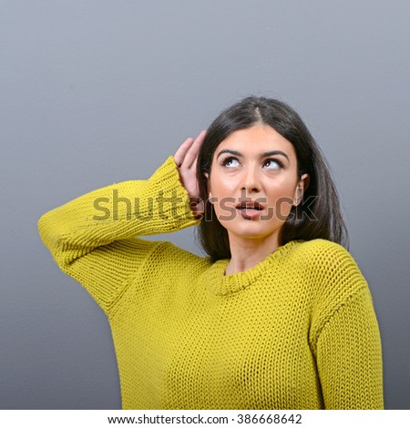 Woman listening with hand to ear concept against gray background - stock photo