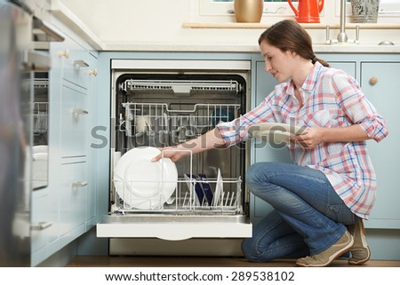 Woman Loading Dishwasher In Kitchen - stock photo
