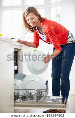 Woman Loading Plates Into Dishwasher - stock photo