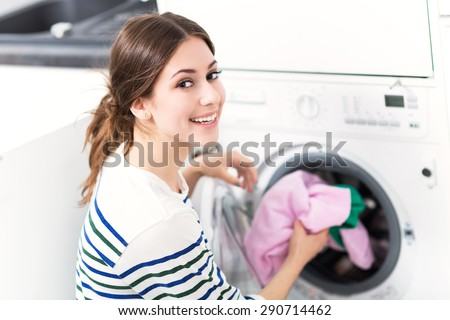 Woman loading washing machine - stock photo