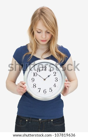 Woman looking at a clock against a white background - stock photo