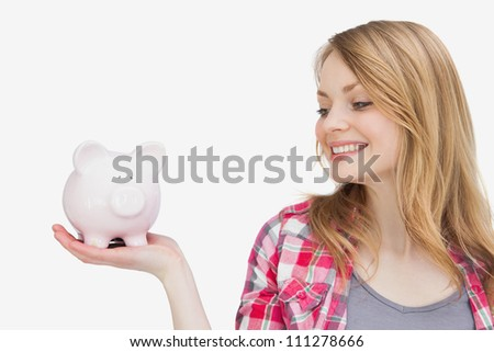Woman looking at a piggy bank on her hand against a white background