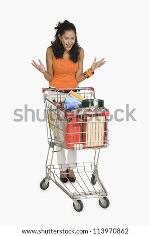 Woman looking at a shopping cart and surprised - stock photo