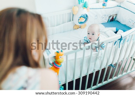 Woman looking at an adorable relaxed baby boy lying in his crib - stock photo