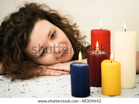 woman looking at candles with head over hands - stock photo