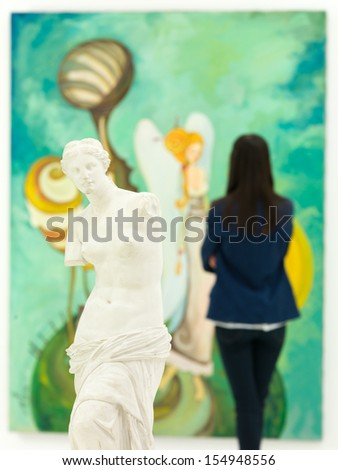 woman looking at colorful large painting behind a replica of Venus de Milo statue - stock photo
