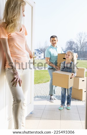 Woman looking at family with cardboard boxes entering new home - stock photo