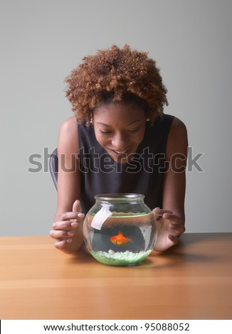 Woman looking at goldfish in bowl - stock photo