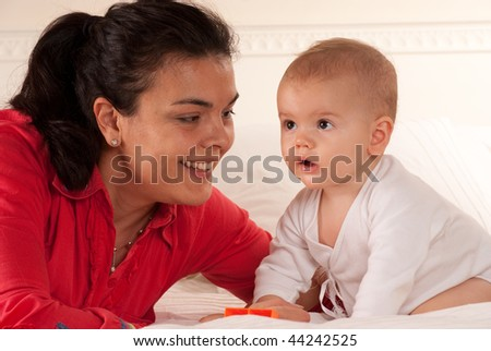 Woman looking at her baby with love - stock photo