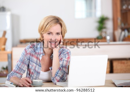 Woman looking at her laptop while drinking a cup of coffee - stock photo
