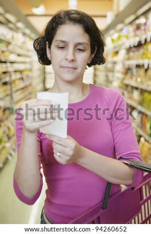 Woman looking at list in grocery store - stock photo