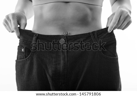 woman looking at loose fitting jeans on white background - stock photo