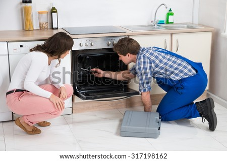 Woman Looking At Male Worker Repairing Oven Appliance In Kitchen Room - stock photo